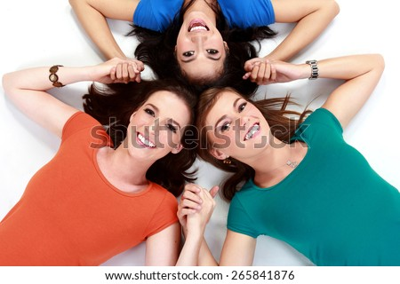 Three passion girls join hands to form stars lying on the floor - stock photo