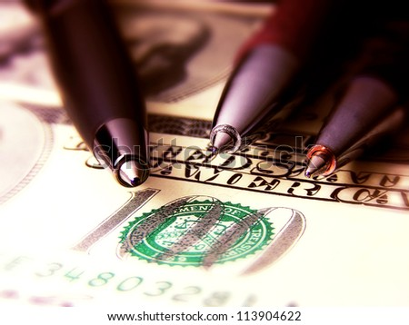 Three pens on a dollar banknote. - stock photo