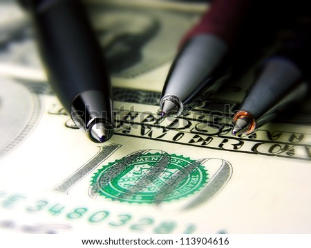 Three pens on a dollar banknote. Small depth of field - stock photo
