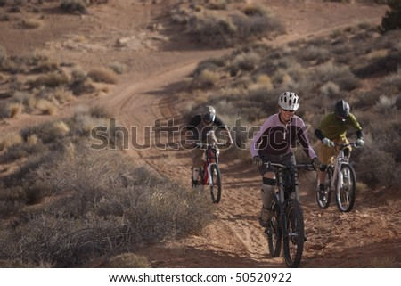 Three people are riding mountain bikes uphill in a desert landscape. Horizontal shot. - stock photo