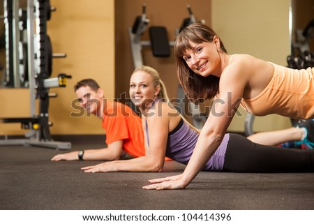 Three People at Fitness Center Preparing for Exercise - stock photo