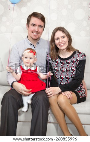 Three people Caucasian family sitting on sofa - stock photo