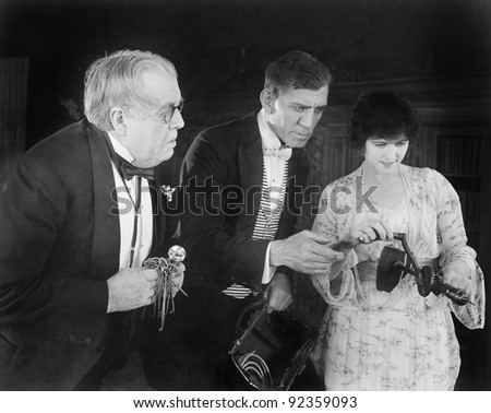 Three people checking out a manual drill - stock photo