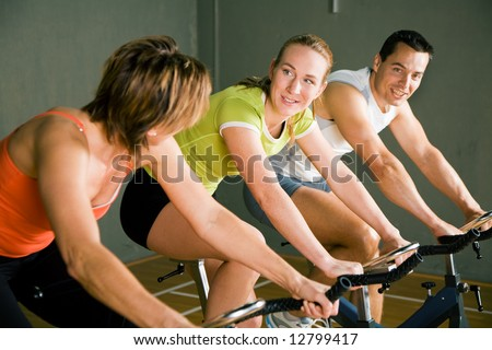 Three people cycling in a gym or fitness club, dressed in colorful clothes; focus on girl in the middle, she is talking to her friend