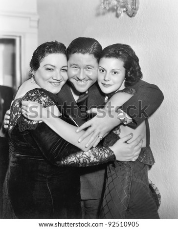 Three people embracing and laughing