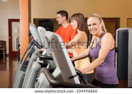 Three People Exercising on Elliptical Trainers - stock photo