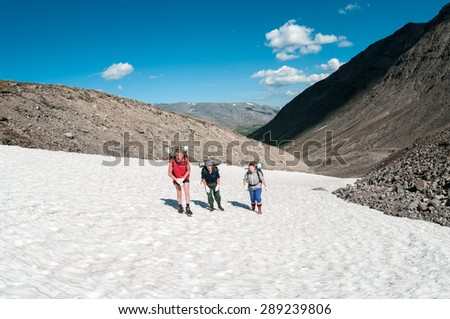 Three people family climbing mountain pass together in the snow at summer - stock photo