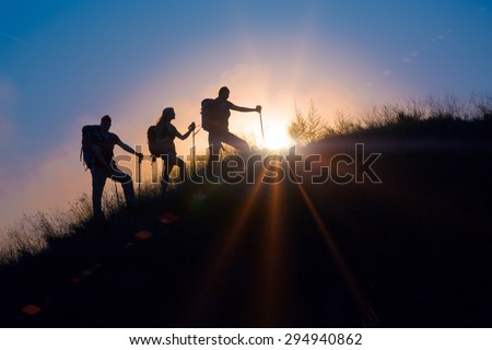 Three people family silhouettes on vacation. Group backpackers moving up toward grassy veld hill uprising colorful sun and rainbow clouds on background