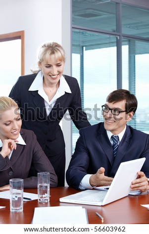 Three people in the office looking at laptop monitor - stock photo