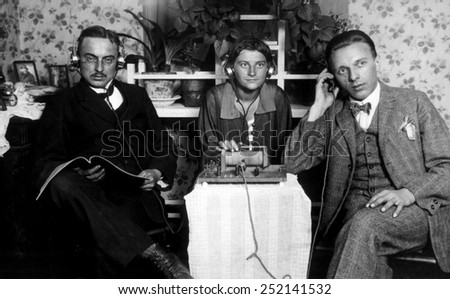 Three people listening to an early radio, c. 1925