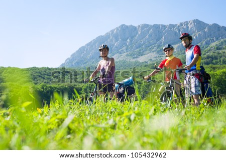 Three people on mountain bikes in the background of the rocky mountains. Bike walk - stock photo