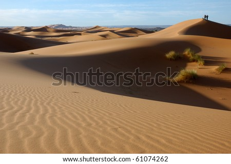 Three people on the top of the dune - stock photo
