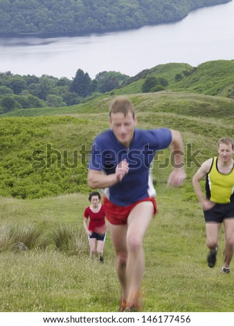 Three people running up country hill - stock photo