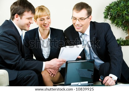 Three people sitting on the sofa and reading the document