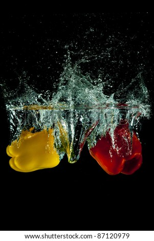 Three peppers water splash on black - stock photo