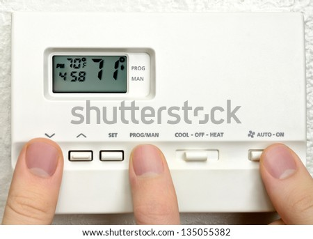 Three persons adjust digital thermostat - stock photo