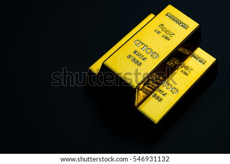 three pieces of gold bar stack up on a black background