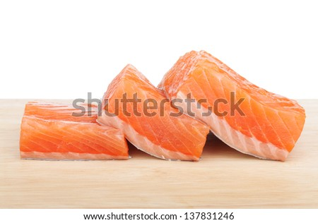 Three pieces of salmon on cutting board - stock photo