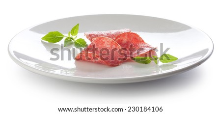 Three pieces of smoked sausage with fresh green basil on the white plate