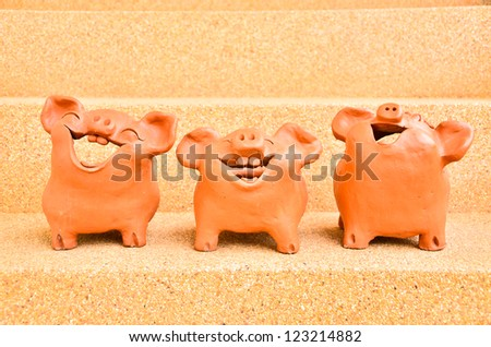 Three Pig statues laugh - stock photo