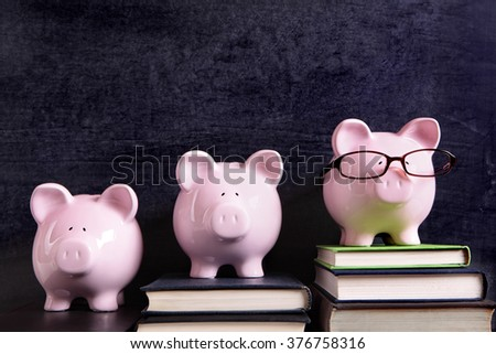 Three piggy banks in a row with blackboard background, college success concept - stock photo