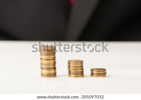 Three piles of golden coins on the table decreasing - stock photo