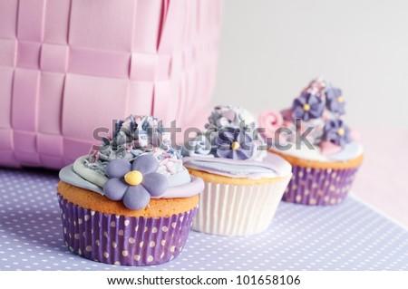 three pink lilac cupcake on a row - stock photo