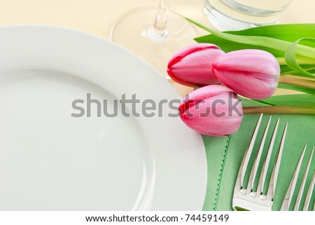 Three pink tulips grace a table setting in fresh Spring colors making a perfect background for Easter or Mother's Day promotions - ample copy space provided with the empty white plate - stock photo