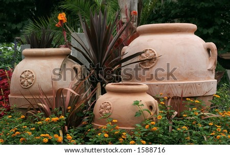 three planting pots and surrounding flowers