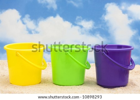 Three plastic buckets on sand with copy space - stock photo