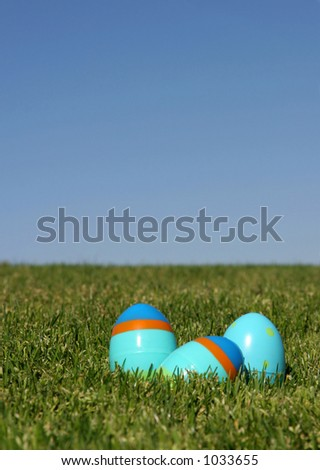 Three plastic Easter eggs on the grass with a blue sky - shallow DOF. - stock photo