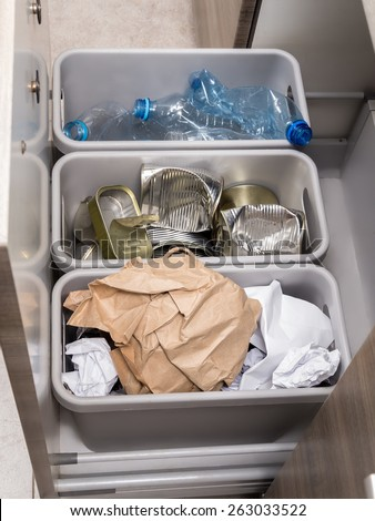 Three plastic trash bins in kitchen cabinet with segregated household garbage - PET bottles, paper and metal cans - stock photo