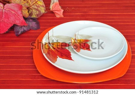 Three plates with the branch of paper autumn leaves - stock photo