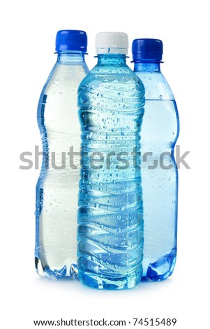 Three polycarbonate plastic bottles of mineral water isolated on white - stock photo