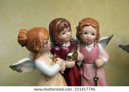 Three porcelain angels in a shop-window.