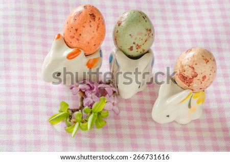 Three porcelain rabbit with eggs and small bouquet of beautiful flowers. Easter still life. - stock photo