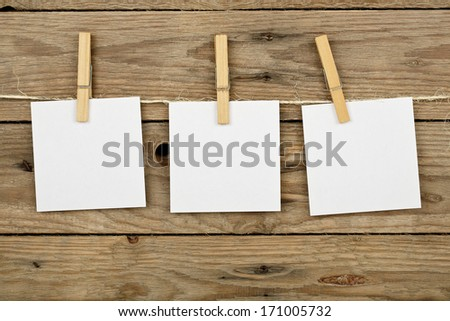 three post-it notes hung with wooden clothes pegs - stock photo