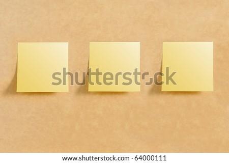 Three post it on brown board texture - stock photo