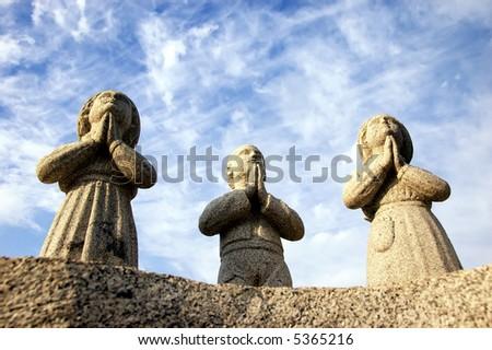 three praying statues - stock photo