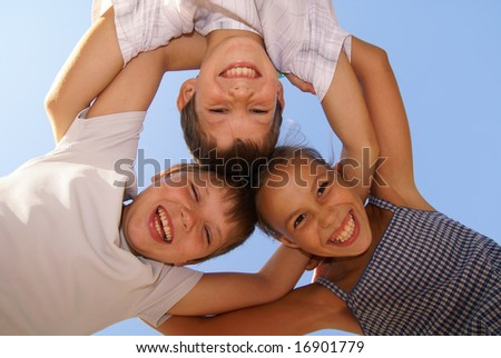 Three preteen friends enjoying summer outdoors on blue sky background - stock photo