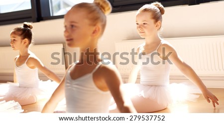 Three pretty young girls in ballet class sitting on the floor in a graceful pose in the white tutus in the warm sunshine - stock photo