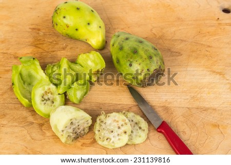 Three Prickly Pears on wooden cutting board with one peeled and being cut for eating. - stock photo