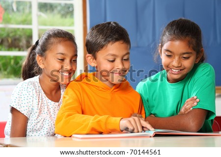 Three primary school children reading and learning together
