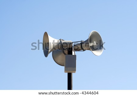 Three public loudspeakers over blue sky - stock photo