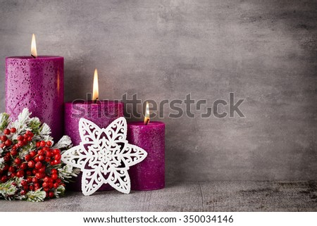 Three purple candles on gray background, Christmas decoration. Advent mood. - stock photo