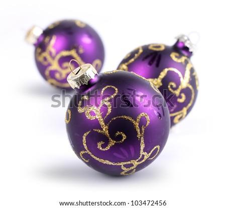 Three purple Christmas balls on white, shallow DOF - stock photo