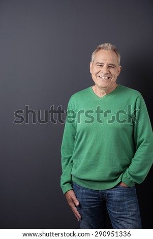 Three-quarter length of happy senior grey haired man with hand in pocket wearing green sweatshirt and denim jeans on black background - stock photo
