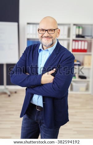 Three Quarter Length Portrait of Casually Dressed Mature Businessman Looking Confident and Smiling at Camera with Arms Crossed in Modern Office Workspace - stock photo