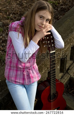 Three Quarter Length Shot of Young Girl Casually Dressed Leaning on Guitar and Looking at the Camera - stock photo