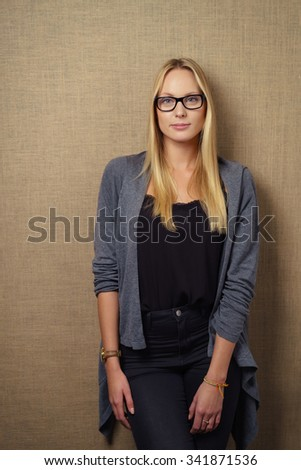 Three Quarter Shot of a Fashionable Young Woman Leaning Against Brown Wall and Looking at the Camera with Half Smile. - stock photo